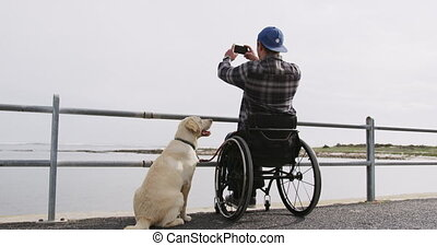 Rear view of a Caucasian man in a wheelchair enjoying taking a walk with his dog in the countryside by the sea, taking a photo in slow motion