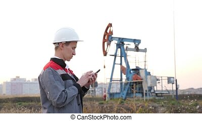 man in a white helmet with a phone against the background of a rocking at an oil well.