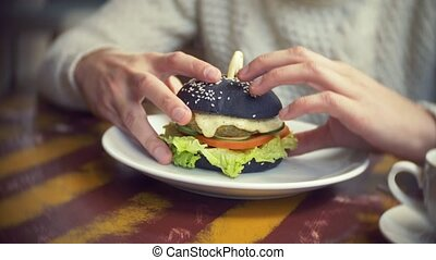 Man in a white sweater eating a black burger in a...