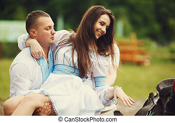 Man in an embroidered blue shirt holds a girl in his hands sitting on the horse