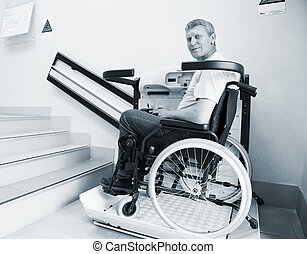 man in an invalid chair walks upstairs on the special...