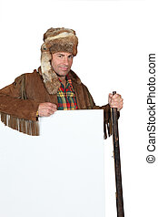 Man in an Western costume with raccoon skin hat and blank board ready for text or image