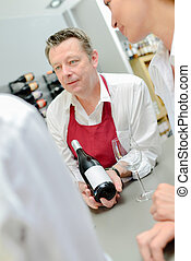 Man in apron showing bottle of wine to couple