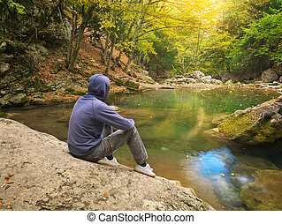 Man in autumn forest and river.