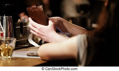 Man in bar pay by credit card from his wallet, telephoto