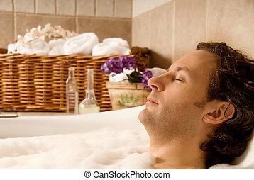 Man in bath - man client in a spa taking an aroma bath