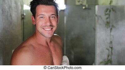 Man In Bathroom Looking In Mirror Fixing Hair, Handsome...