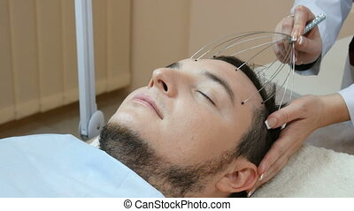 woman doing head massage with massager for male client