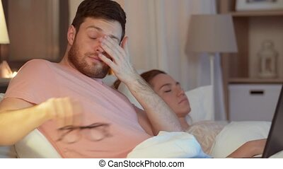 man in bed closing laptop and turning light off