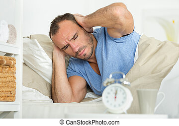 man in bed covering his ears as the alarm sounds