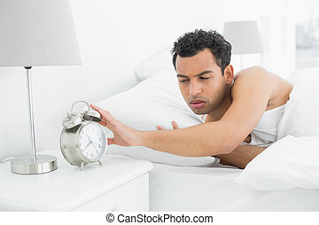 Man in bed extending hand to alarm clock