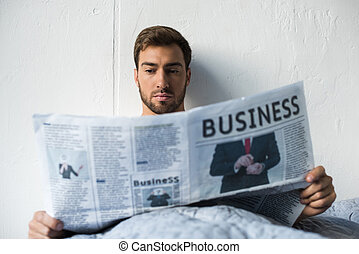 Man in bed reading newspaper
