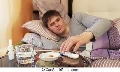 Man in bed with a flu checking temperature