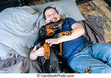 Man in bed with big dog