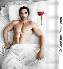 Man in bed with rose - Portrait of a sexy muscular male...