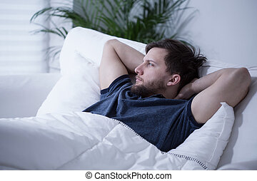 Man in bed - Young handsome man lying in bed at day