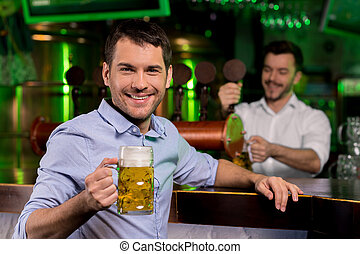Man in beer pub. Handsome young man holding a beer mug and smiling while bartender pouring beer on the background