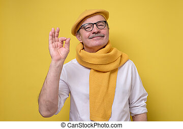 man in beret and scarf looking with a smile at camera ...
