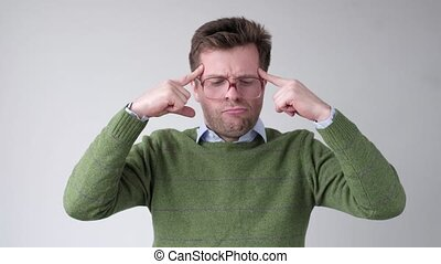 Man in big glasses holds fingers on temples, trying to remember or generate idea.
