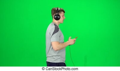 Man in big headphones goes and texting with smartphone on green screen at studio. Side view