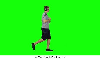 Man in big headphones is running, Chroma Key. Profile side view