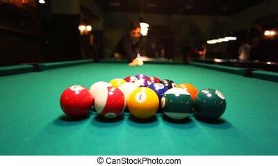 man in billiards breaks balls