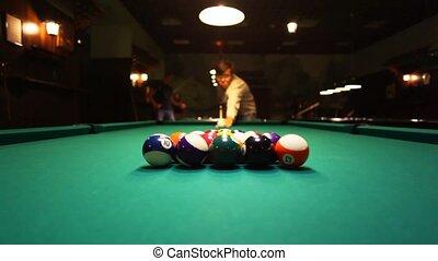 man in billiards shoots at balls