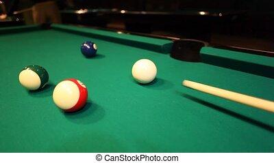 man in billiards shoots blue ball in pocket