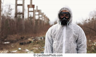 Man in bio-hazard suit and gas mask stands before the factory