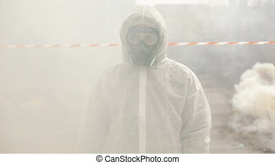 Man in bio-hazard suit and gas mask stands in the smoke