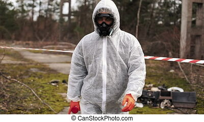 Man in bio-hazard suit and gas mask walks to the stipe on...