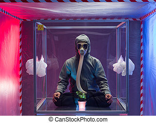 Image of a man sitting inside a box wearing biohazard suit and mask.