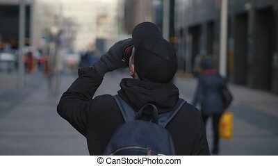 Man in black cap and backpack drinking hot coffee during...