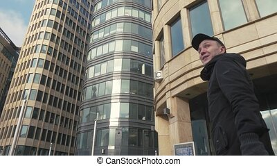 Man in black cap walking on city street and waving hand for greetings