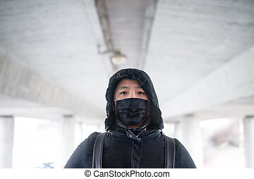 Man in black clothes and mask standing outdoors in city, coronavirus concept.