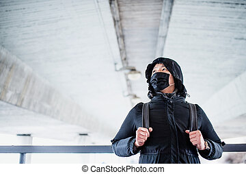 Man in black clothes and respirator standing outdoors in city, coronavirus concept.