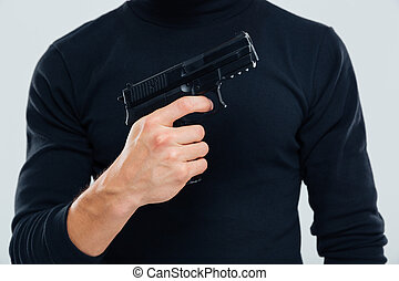 Man in black clothes standing and holding a gun - Closeup of...