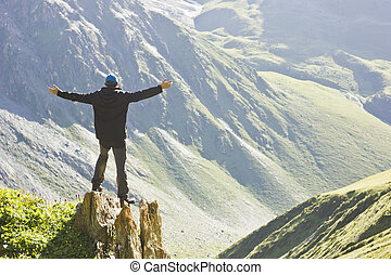 man in black jacket standing on stone with hands-up above mountais at sunset