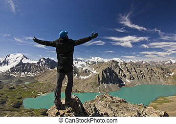 man in black jacket standing with hands-up above blue lake in mountains