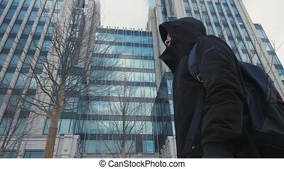 Man in black jacket with hood on head and backpack walking city street