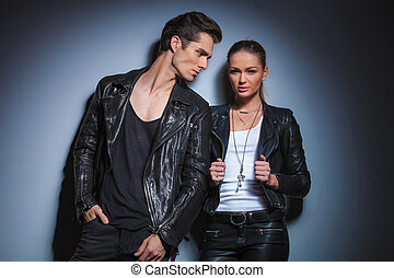 man in black looking at his woman while she is posing arranging her jacket