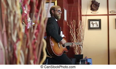 man in black plays guitar among curtains