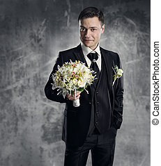 Man in black suit with flowers bouquet. Wedding groom fashion. Gray background.