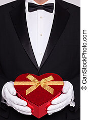 Man in black tie holding a heart shaped box of chocolates