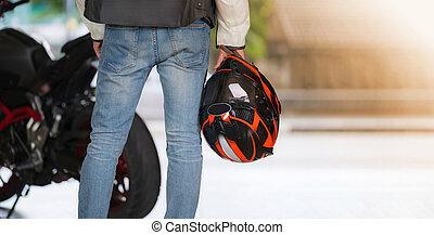 Man in blue jean holding a helmet