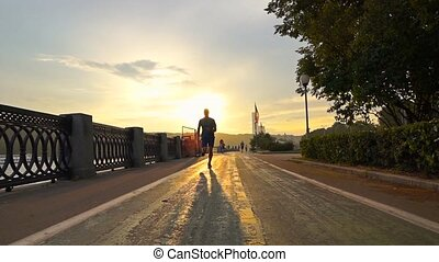 Man in blue running on summer sunset embankment at the camera, Moscow. Super slow motion steadicam shot at 240 fps