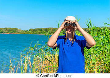 man in blue shirt is looking out for prey with binoculars
