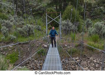 Man In Blue Shirt Stands On Suspension Bridge