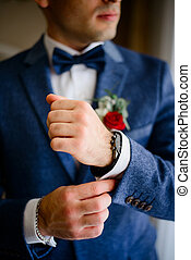 Man in blue suit adjusts white sleeve over black watch