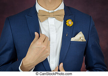 man in blue suit bowtie, brooch, handkerchief